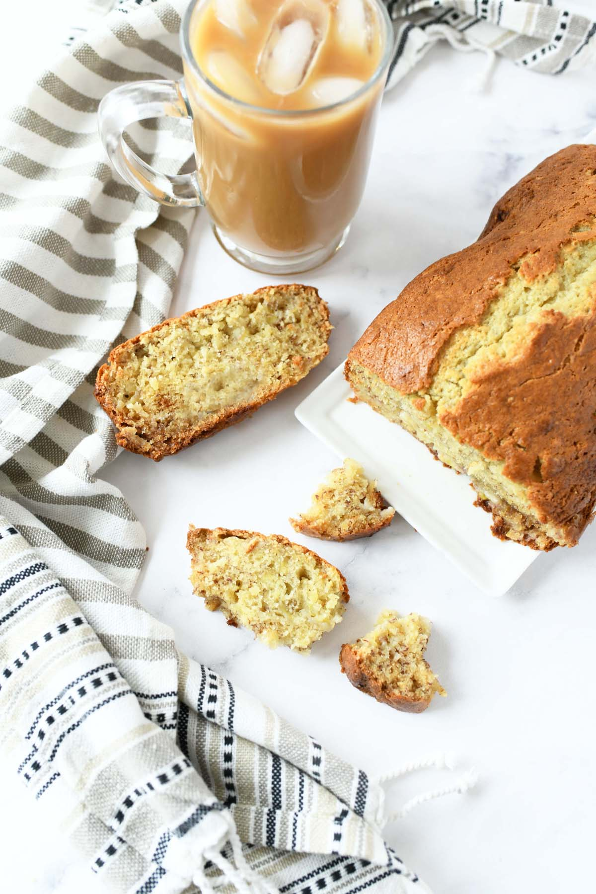 Banana Bread made with Sour Cream. Bread is sliced on a white marble table with a cup of coffee nearby.