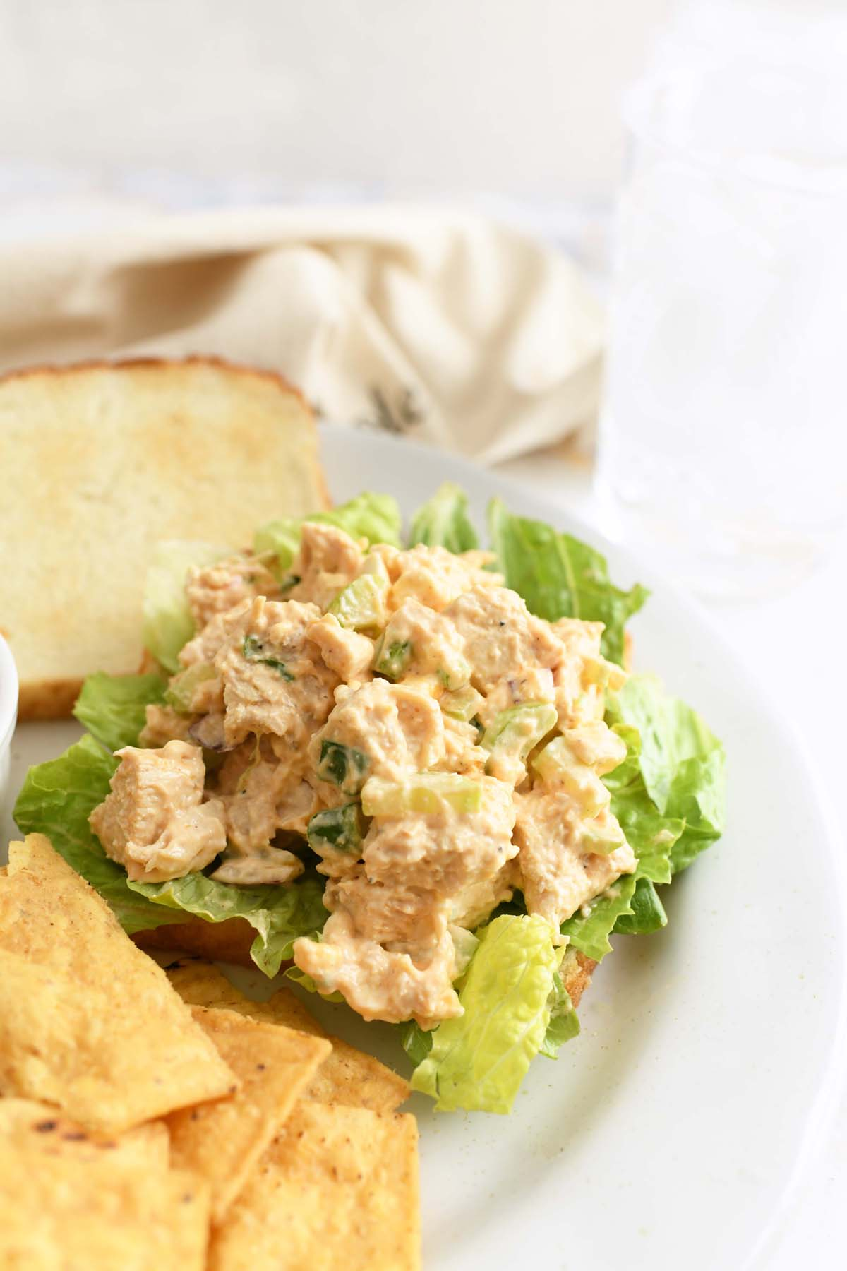 Buffalo Chicken Salad Sandwich. A toasted sandwich has chicken salad on it with lettuce. There are corn chips on the plate as well.