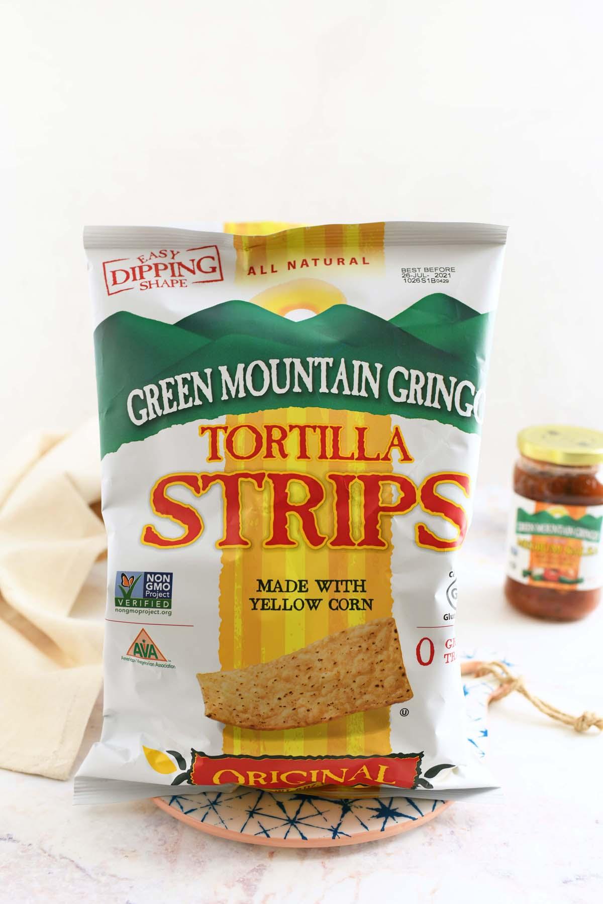Green Mountain Gringo Tortilla Strips. A bag of tortilla strips on a white table with a tan napkin.