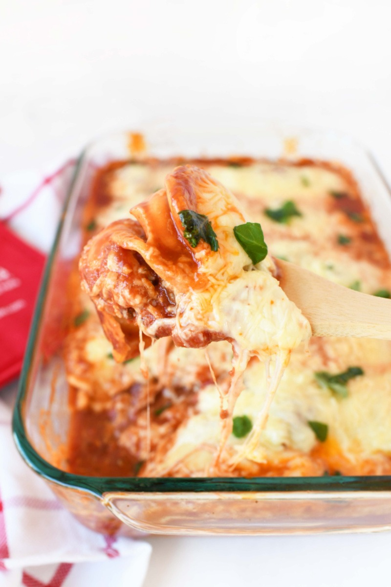 Lasagna with Ravioli- A baked, cheesy dish with a hearty helping on a wooden spoon.
