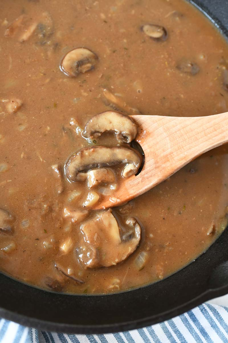 Mushroom Gravy- Brown mushroom on a wooden spoon. There is a blue striped napkin in the shot.
