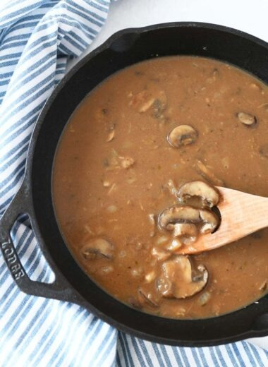 Mushroom Salisbury Steak Gravy is in a black cast iron pan with a blue and white striped napkin.