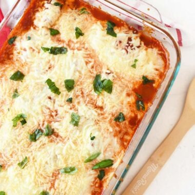 Ravioli Lasagna Recipe baked in a deep dish Pyrex. There is a red checkered napkin and a wooden spoon in the image.