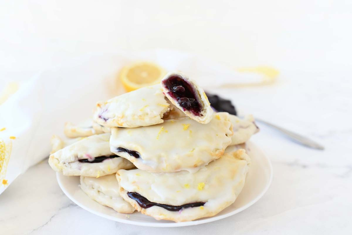 Blueberry hand pies with lemon zest on top, opened up.