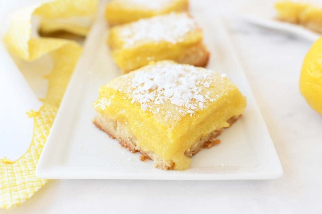 Sugar dusted, yellow easy Lemon Bars on a white plate with a yellow napkin.