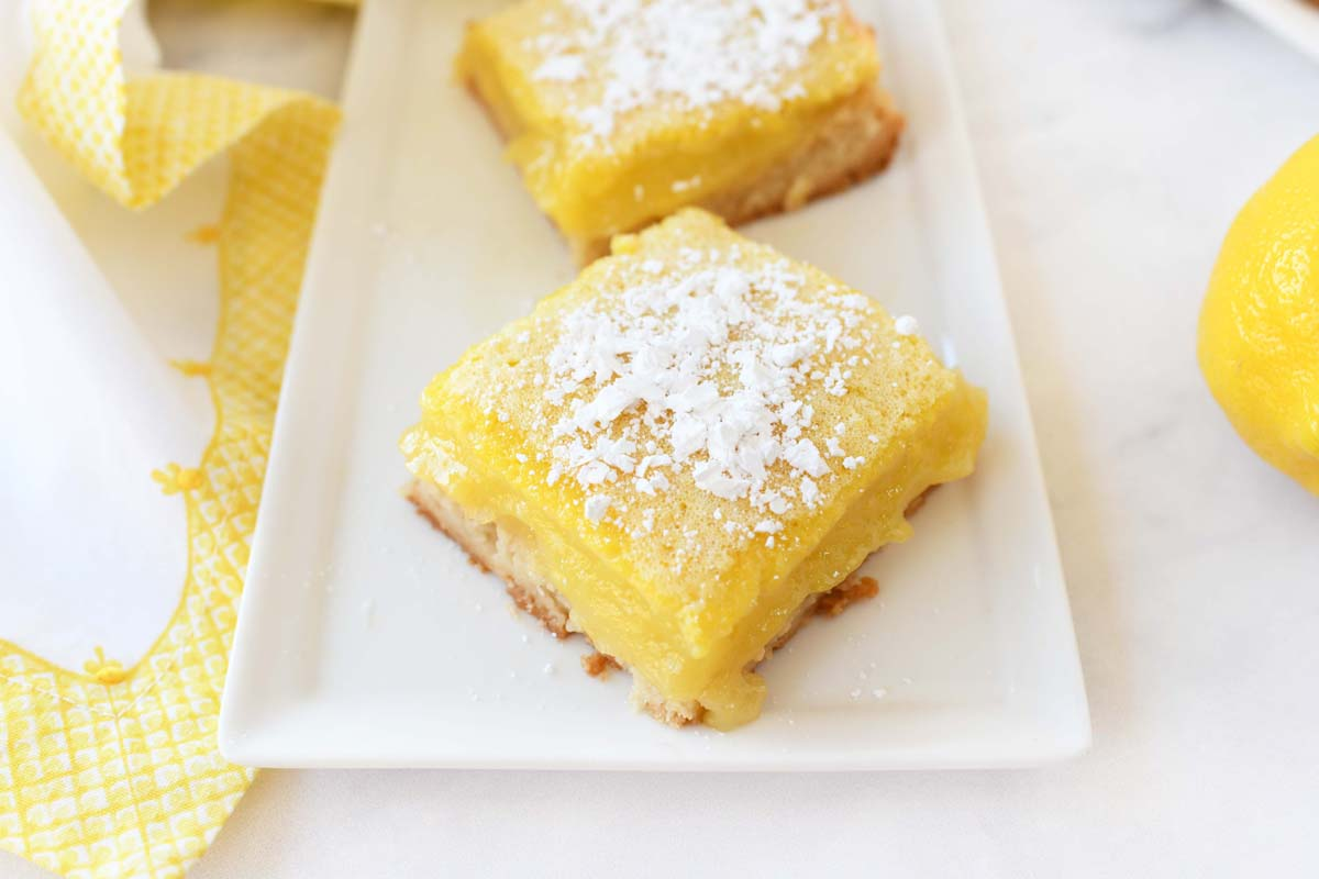 Powdered sugar dusted lemon squares on a white, rectangle plate.
