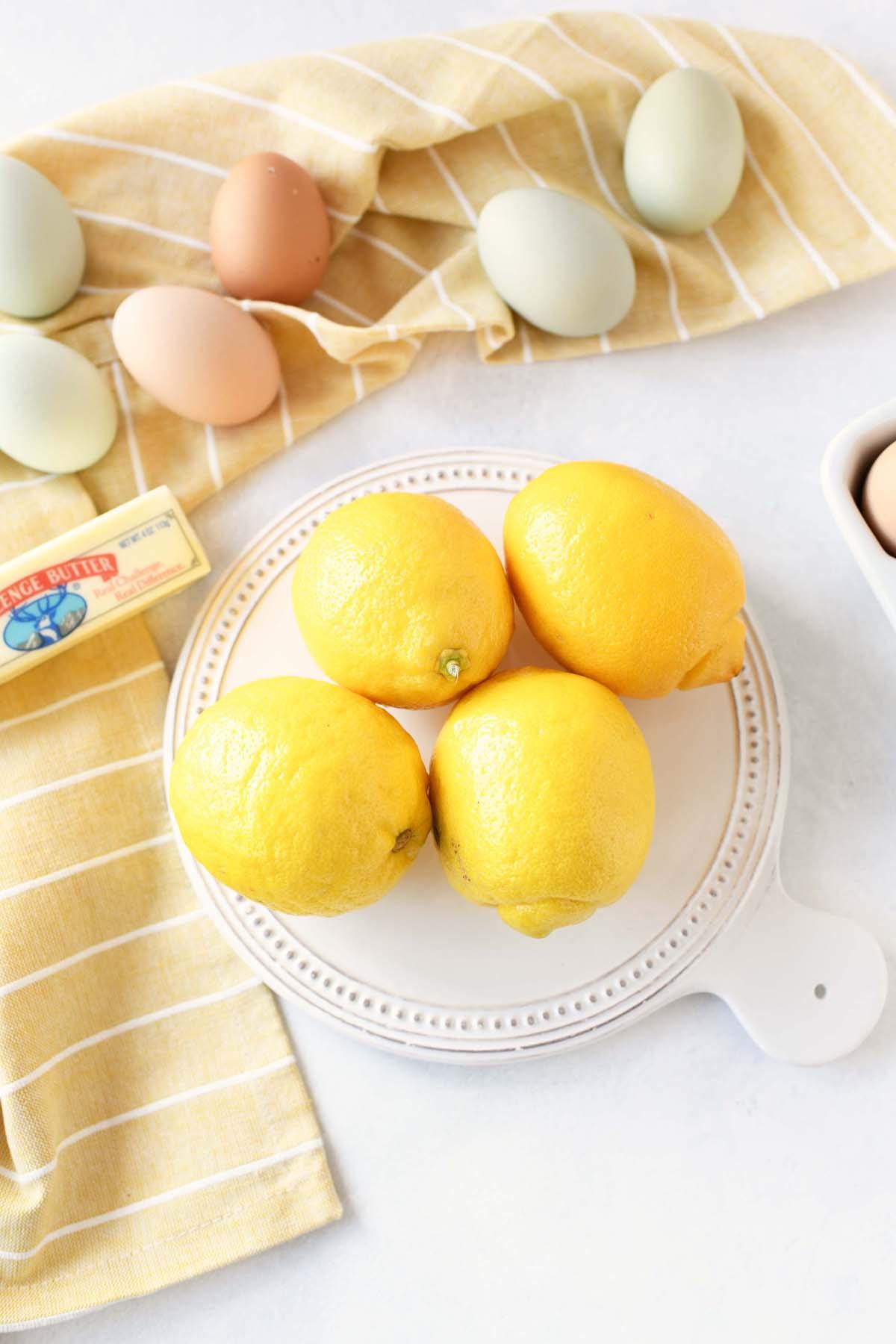 Fresh lemon curd ingredients like eggs, butter, and lemons on a white table.