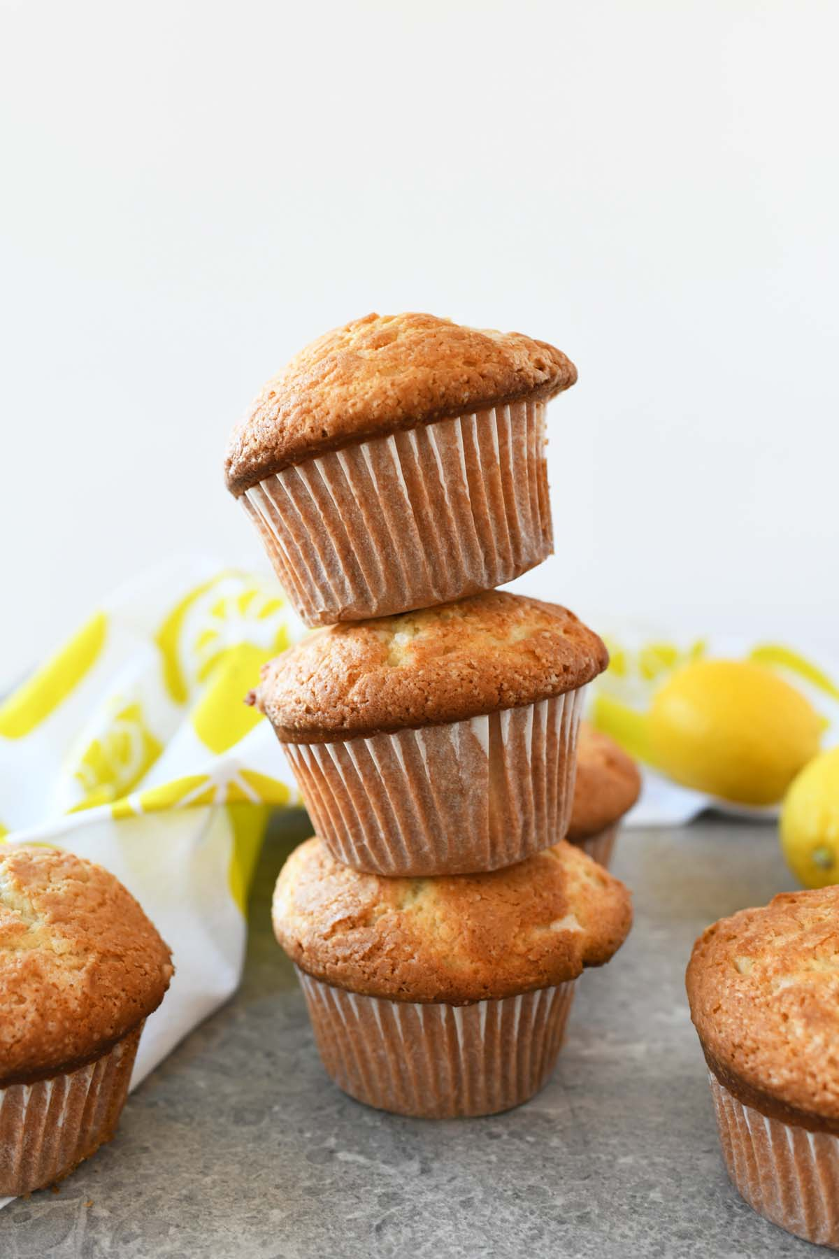 Iced Jumbo Lemon Muffin Recipe are stacked on a grey table with a lemon napkin in the background.
