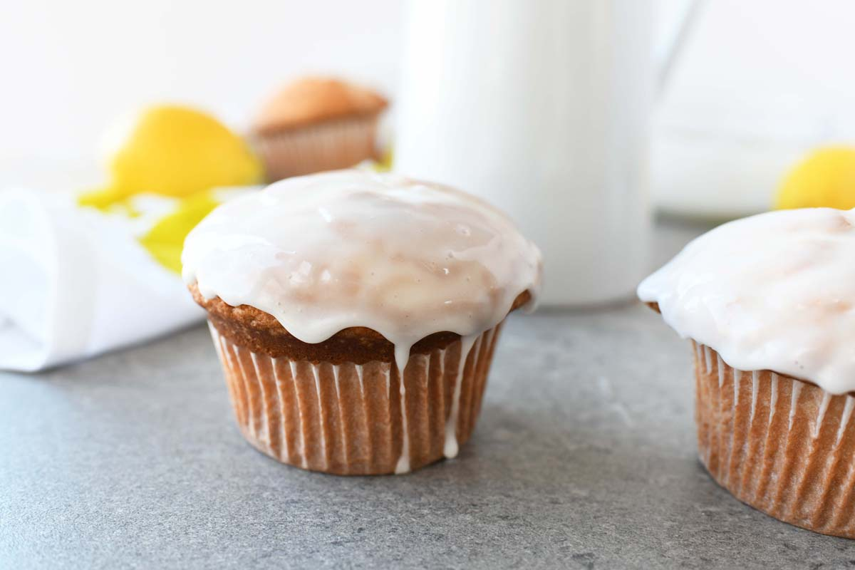 Iced Lemon Cupcakes on a grey table. There is a milk jug and a fresh lemon in the background.
