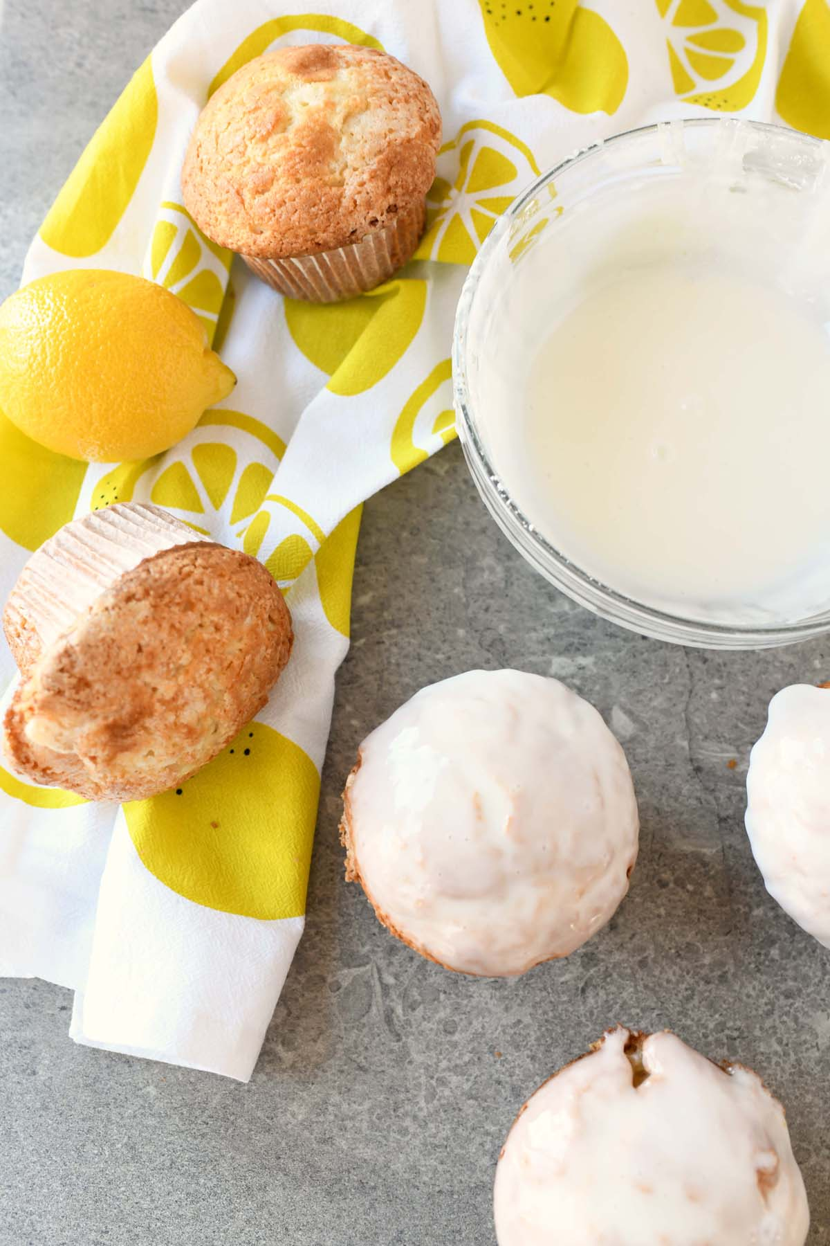 Iced and plain Lemon Jumbo Muffins on a grey table. There is a lemon napkin and a bowl of icing in the shot.