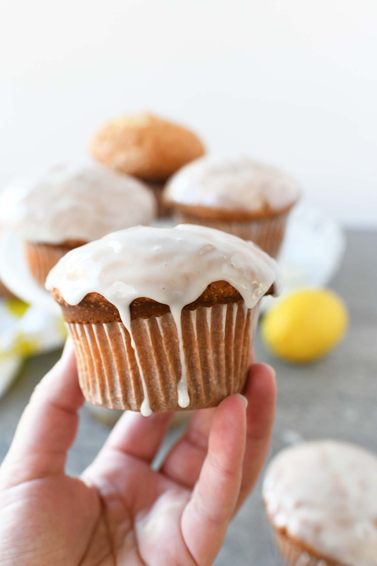 Iced Lemon Muffin in someone's hand. The icing is dripping down the wrapper.