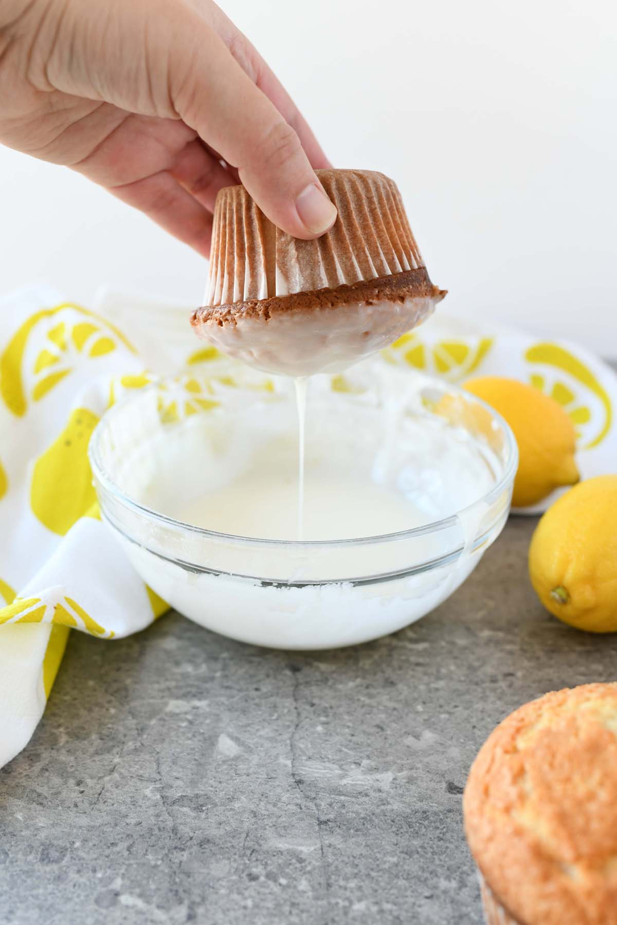 Iced Lemon Muffins Recipe. A plain lemon cupcake being dipped into icing.