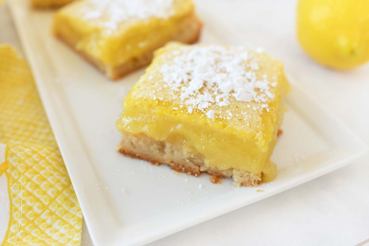 A shot of a sugar dusted lemon bar up close on a white plate.
