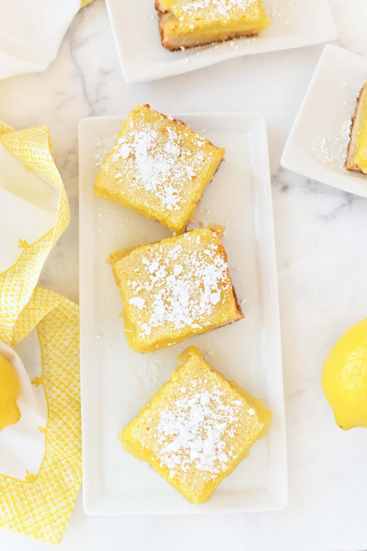 Lemon Bars cut on a white rectangle dish with a yellow napkin and fresh lemon nearby.