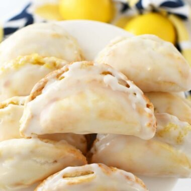 Lemon Curd Hand Pies on a white tray with a lemon napkin nearby.