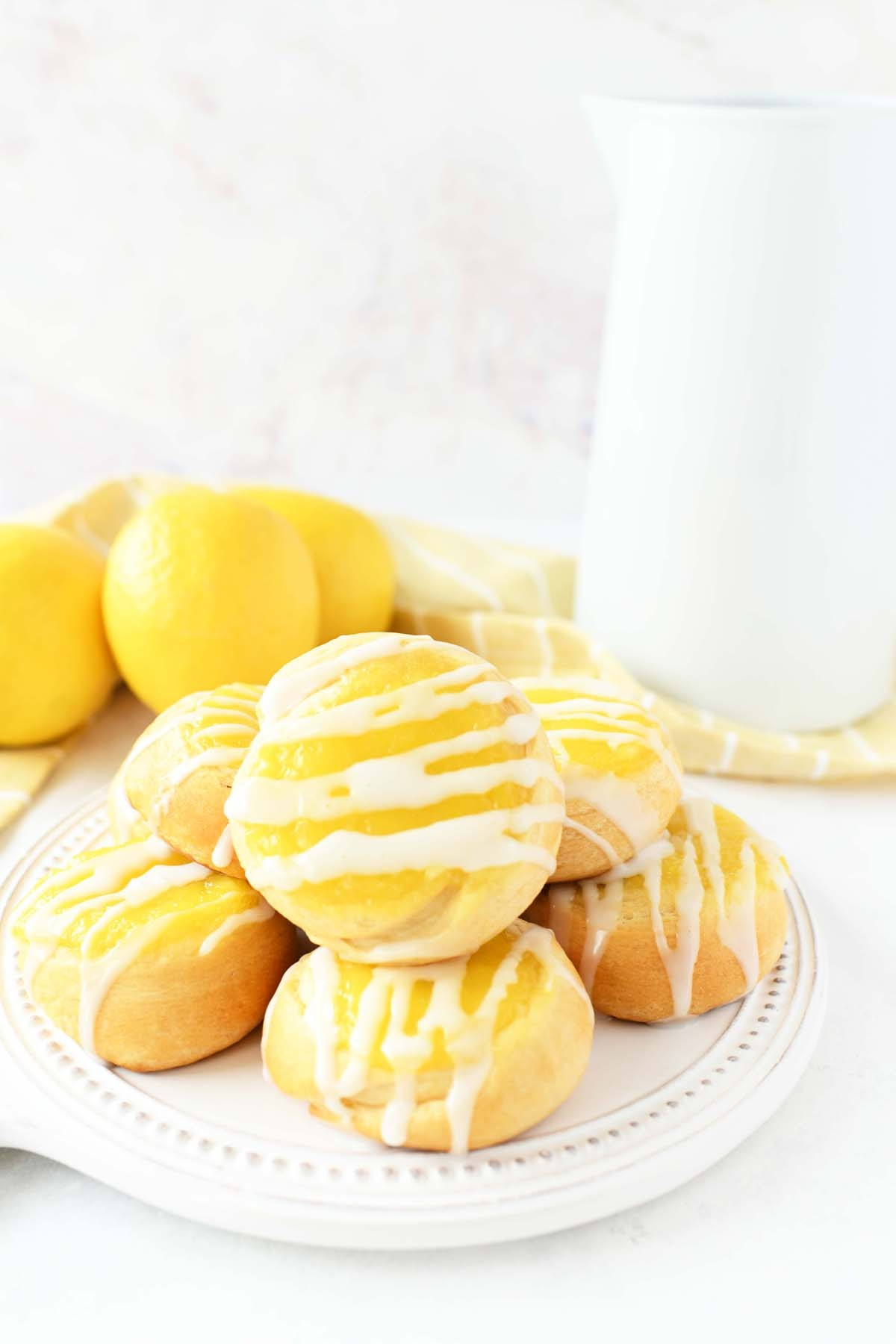 Lemon Danish with with icing on a white plate with fresh lemons.