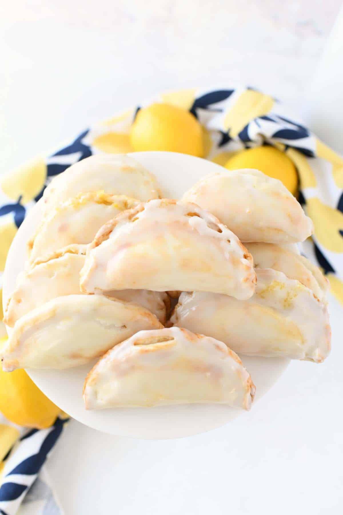 Lemon Hand Pies on a white plate with a lemon themed napkin.