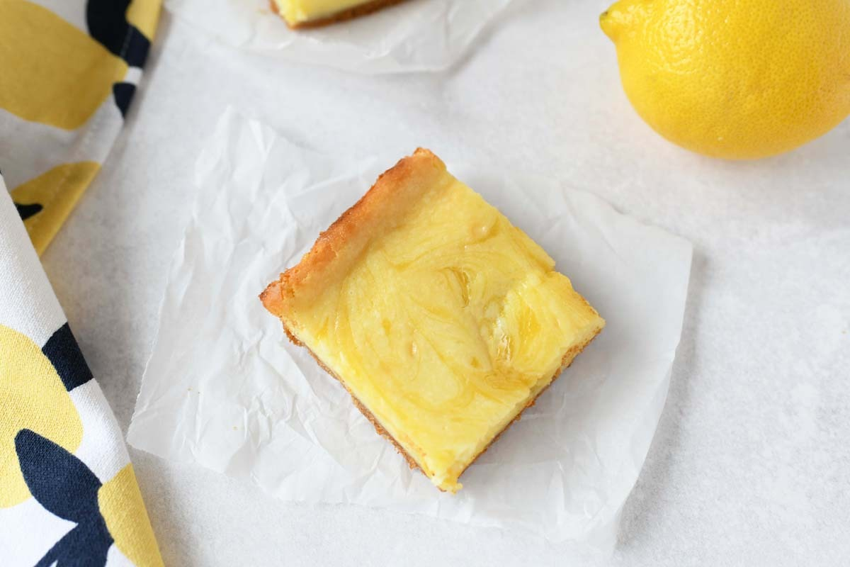 Lemon Swirled cheesecake square on a piece of white parchment paper.