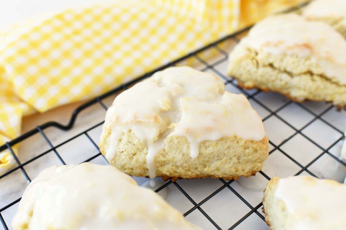 Glazed lemon scones on a black wire baking rack with a yellow checkered napkin.