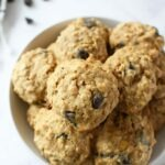 Banana Chocolate Chip Cookies stacked in a white bowl with scattered chocolate chips around.