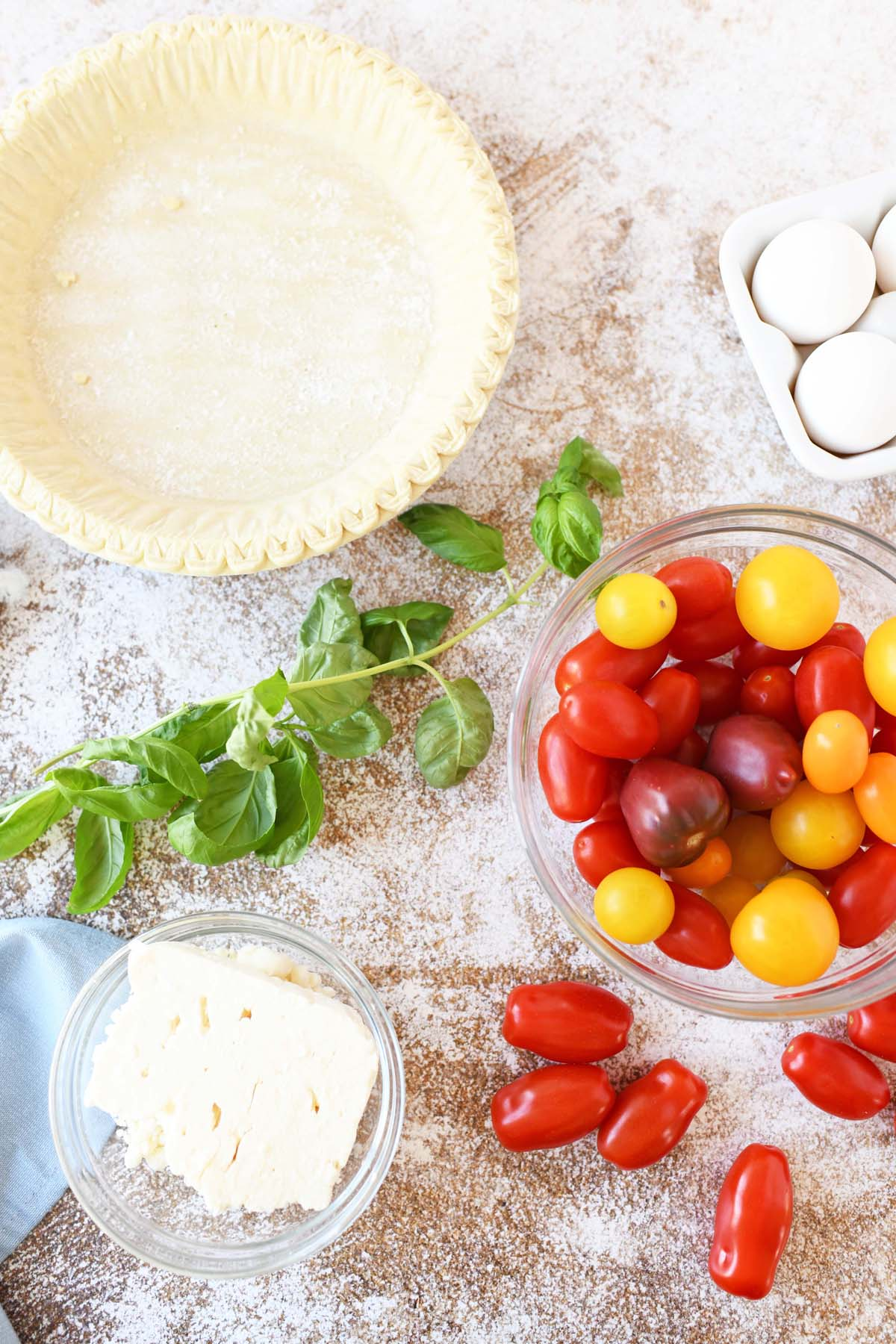 Feta, tomato, pie crust, and basil on a speckled table.