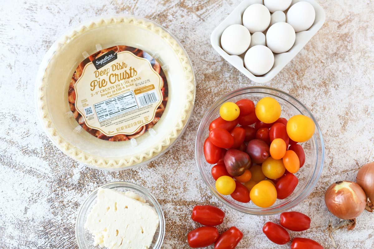 Frozen pie crust with tomato, eggs, and feta on a table.