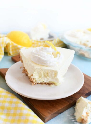 A fresh slice of lemonade no-bake pie on a small, white plate with a bite missing.