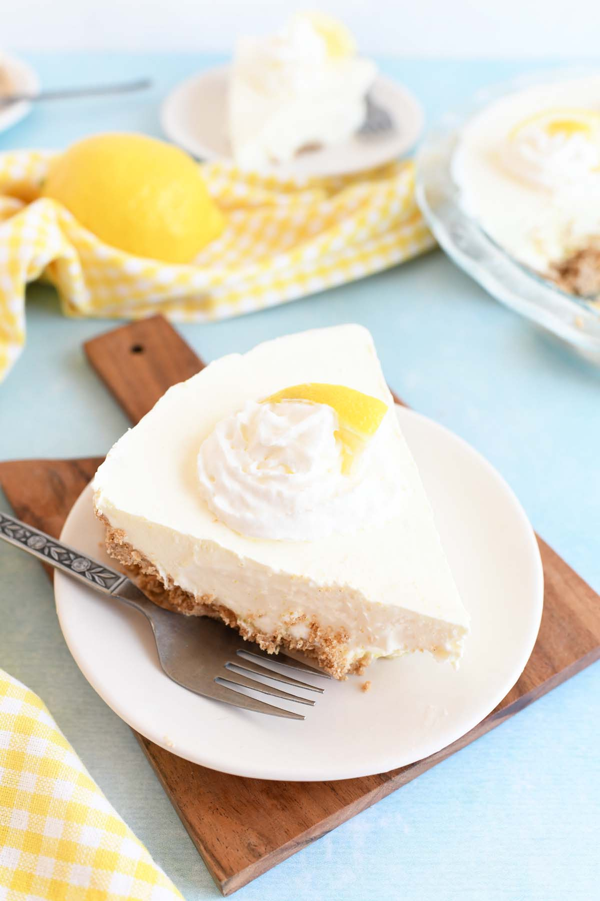 Lemon Jello Pie on a small white plate with a wooden cutting board and fork.