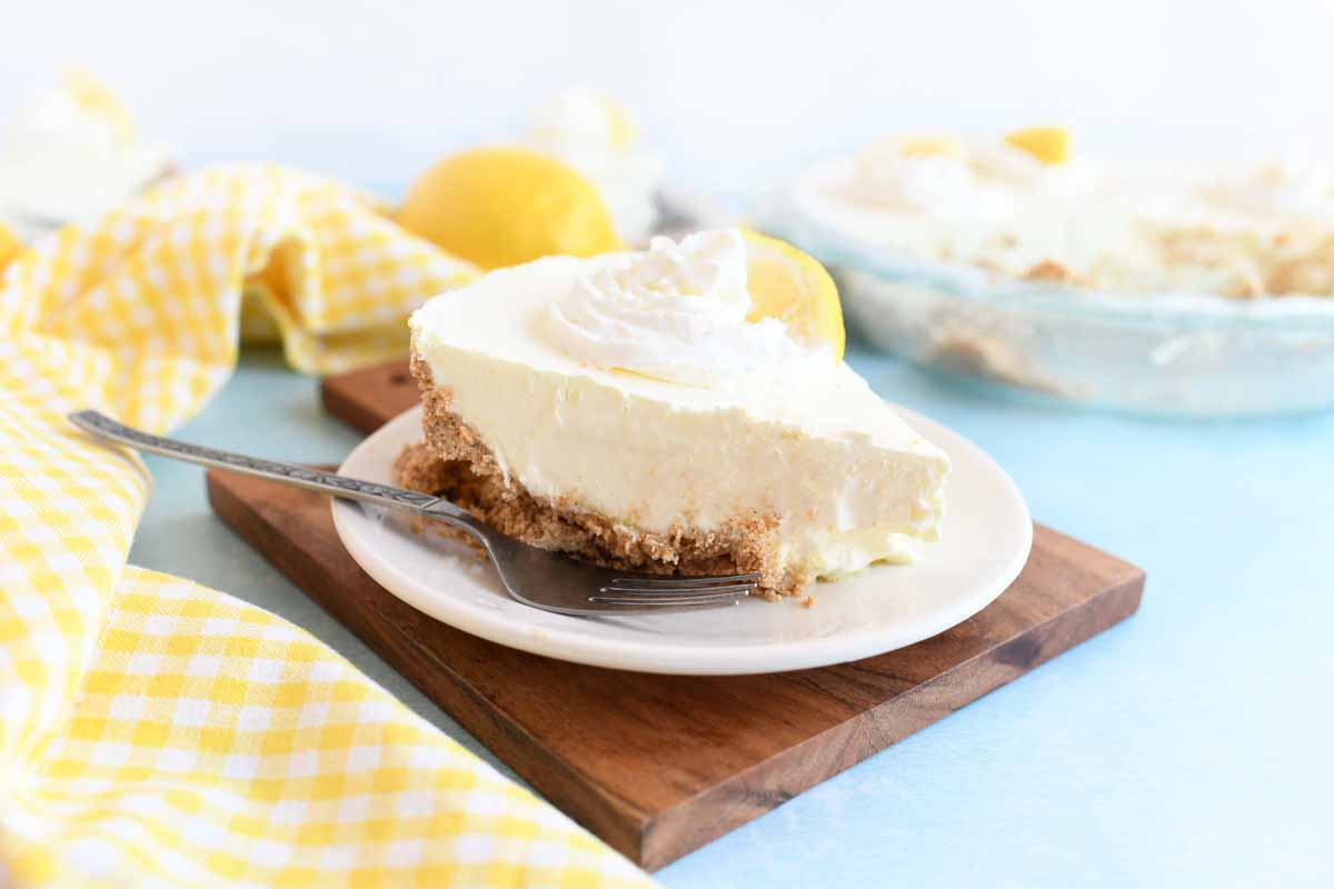 Lemonade Pie with whipped cream and a small lemon wedge on top.