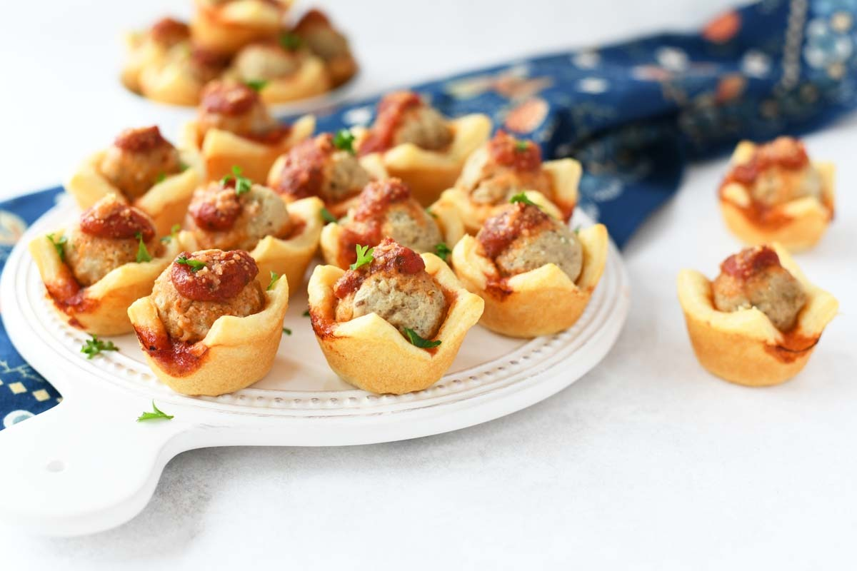 Meatball Bites with sauce and cheese on a white tray with a blue floral napkin.