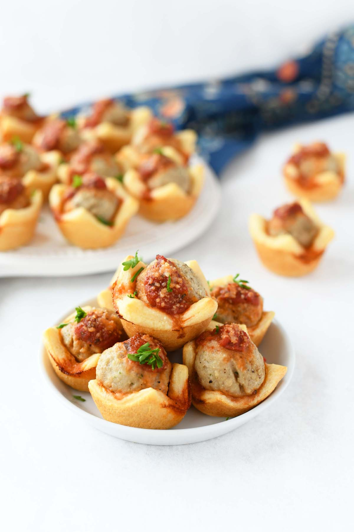 Meatball Crescent Bites on a small white platter with a blue, floral napkin.