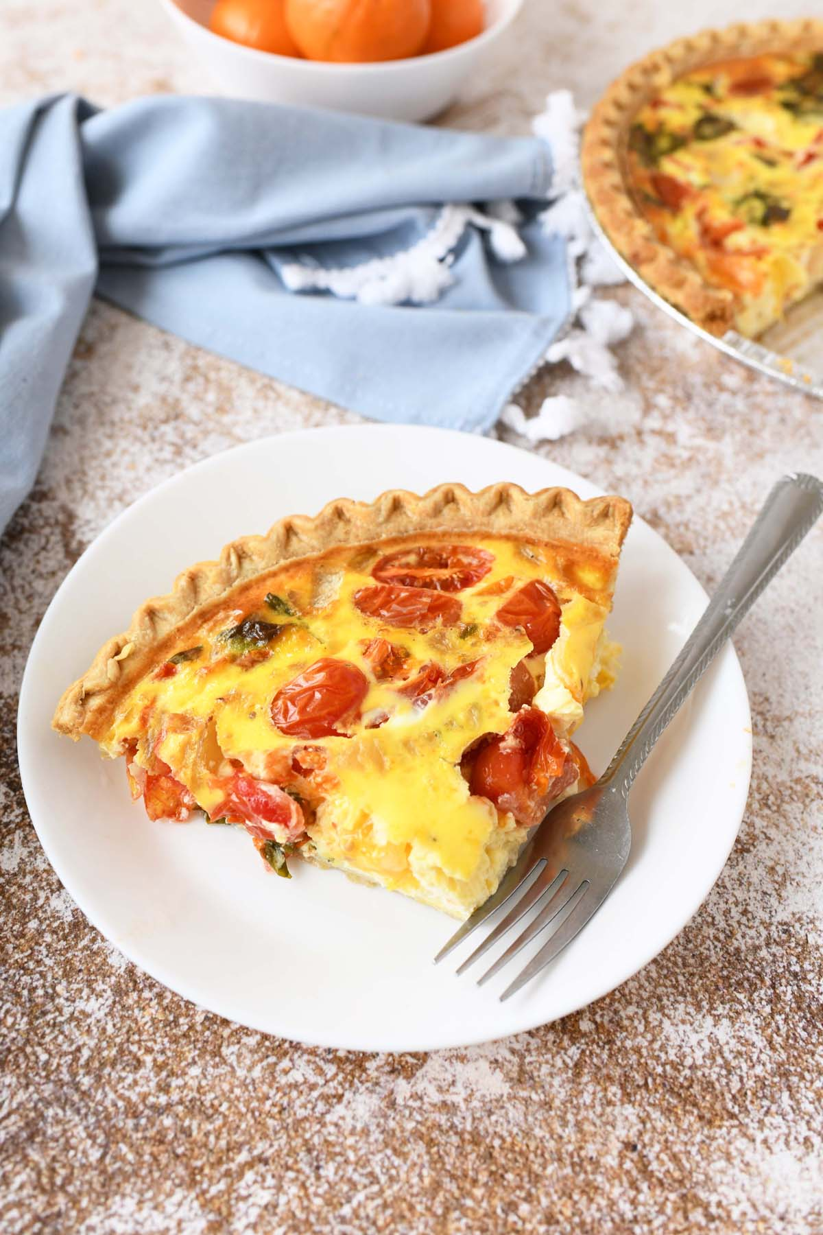 Tomato Feta Quiche on a white plate with a fork.