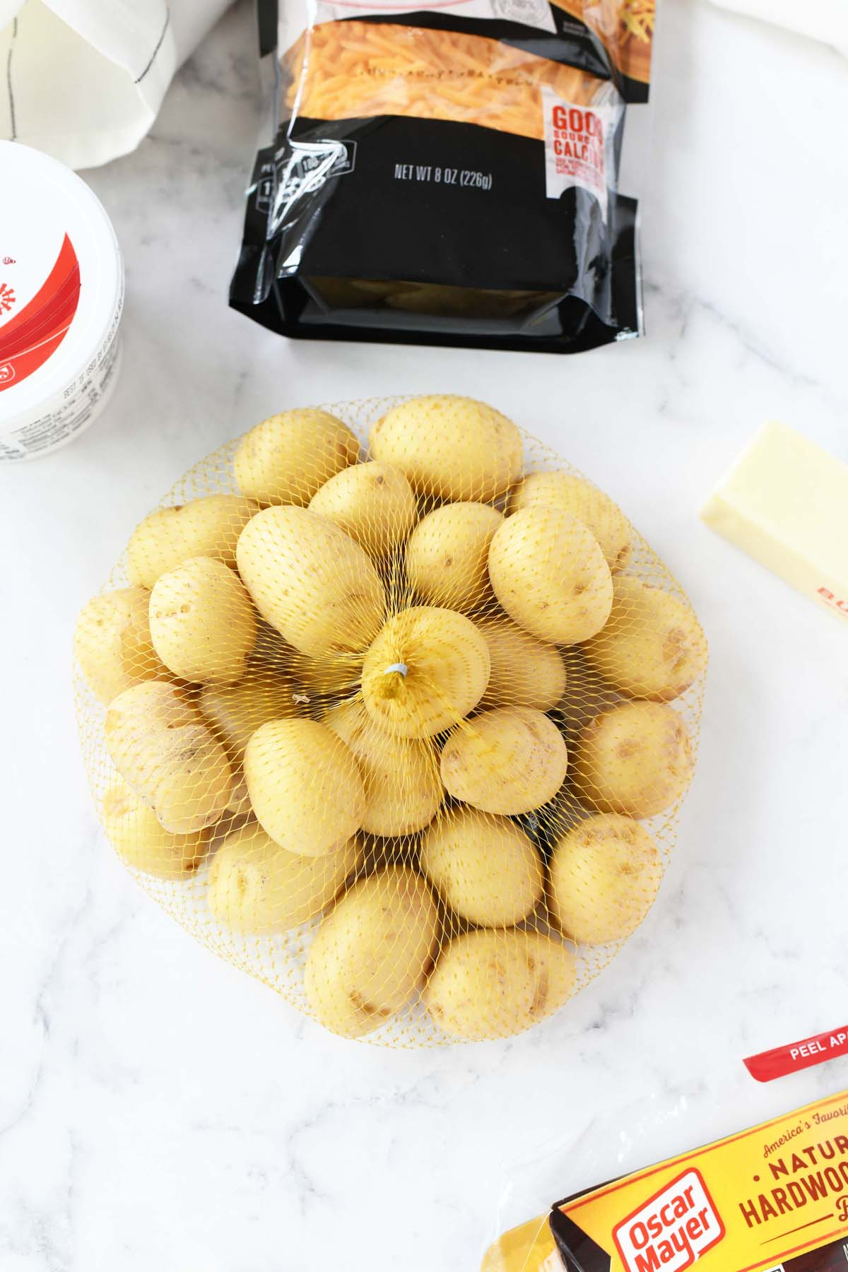 Baby potatoes in a netted bag on a white table.