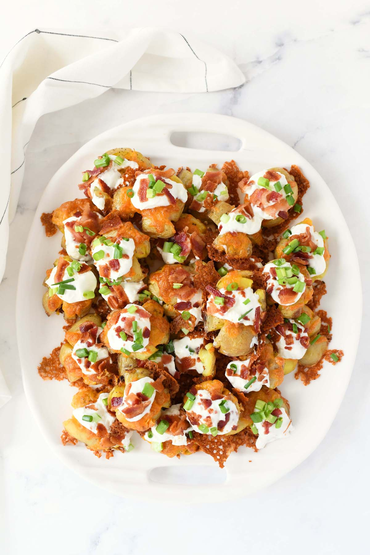 Cheesy Bacon smashed potatoes on an oval serving tray with a white napkin.