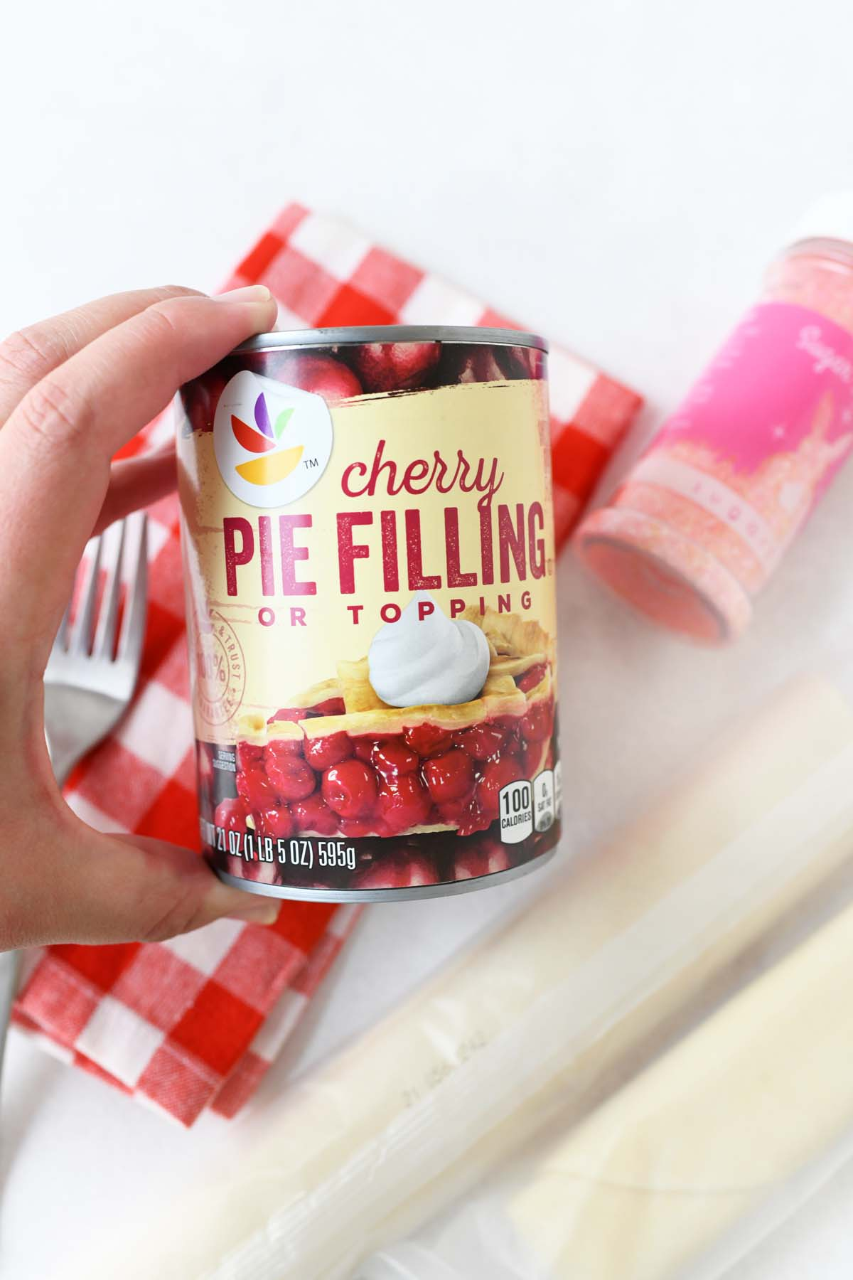A hand holding a can of cherry pie filling.