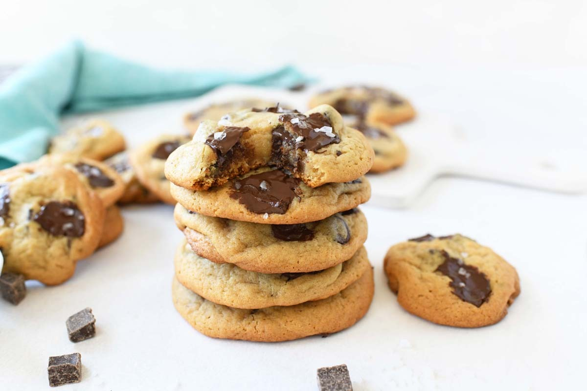 A stack of salted chocolate chunk cookies on a white table.