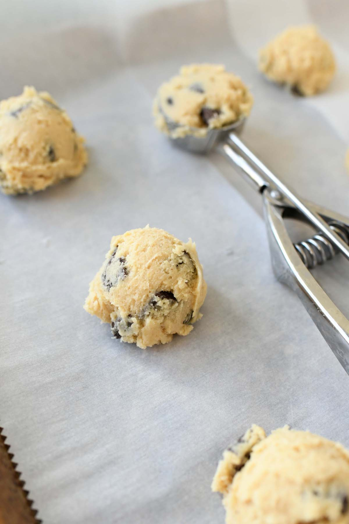 Chocolate Chip Cookie dough balls with a cookie scoop on a baking sheet.