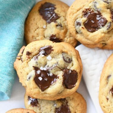 Salted Chocolate Chunk cookies stacked on a white plate.