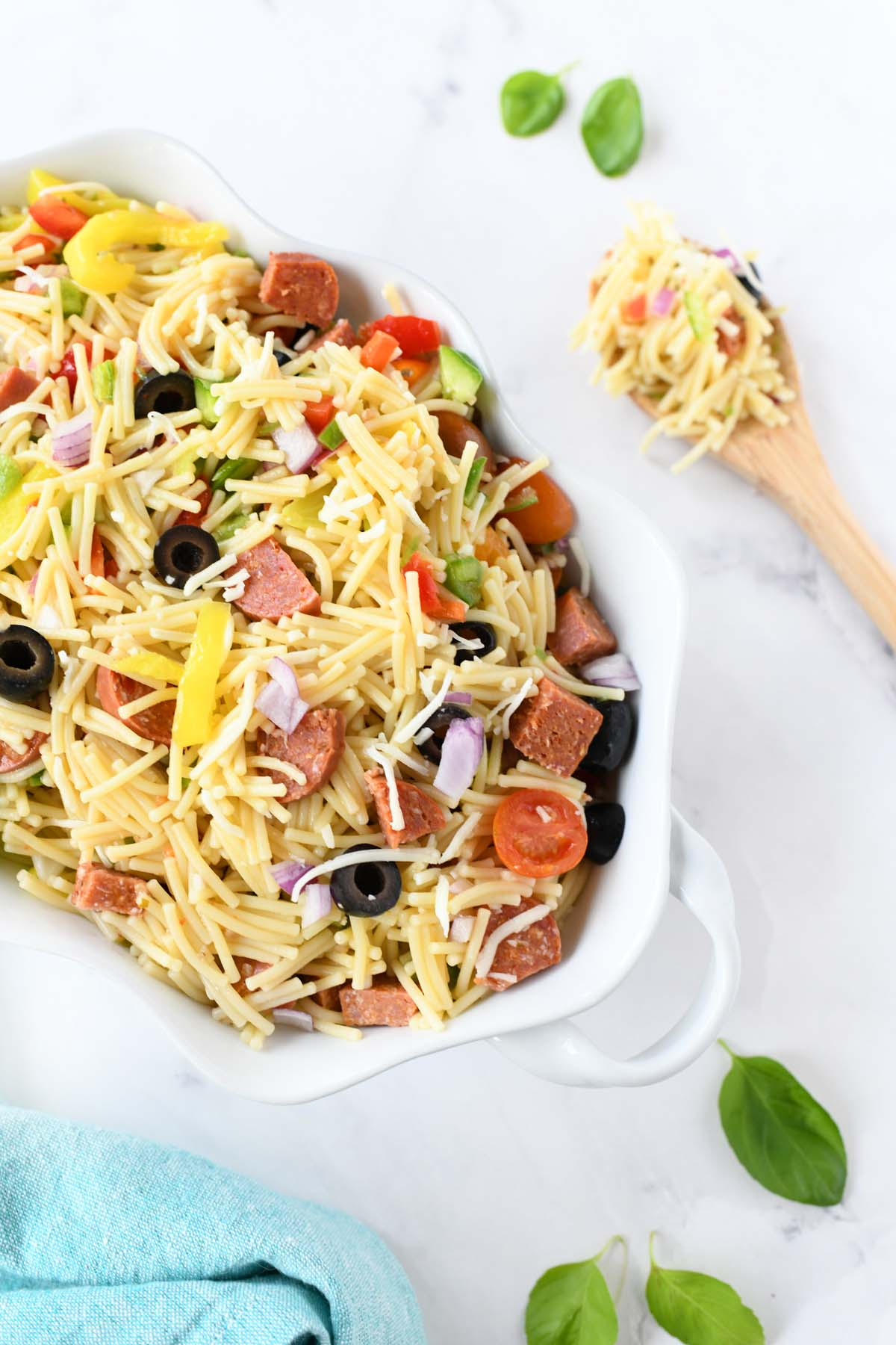 Cold Pizza Pasta Salad in a white dish with a wooden spoon.