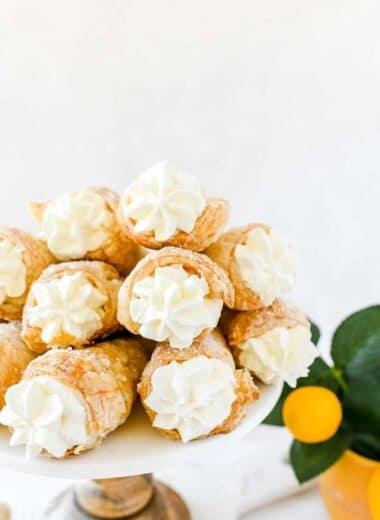 Lemon cream horns stacked on a white tray.