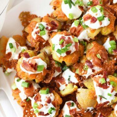 Crispy, cheesy, loaded smashed potato bites on a white platter.