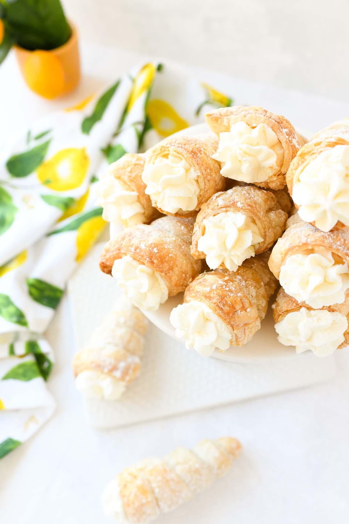 Lemon cream horns on a white platter near a lemon napkin.