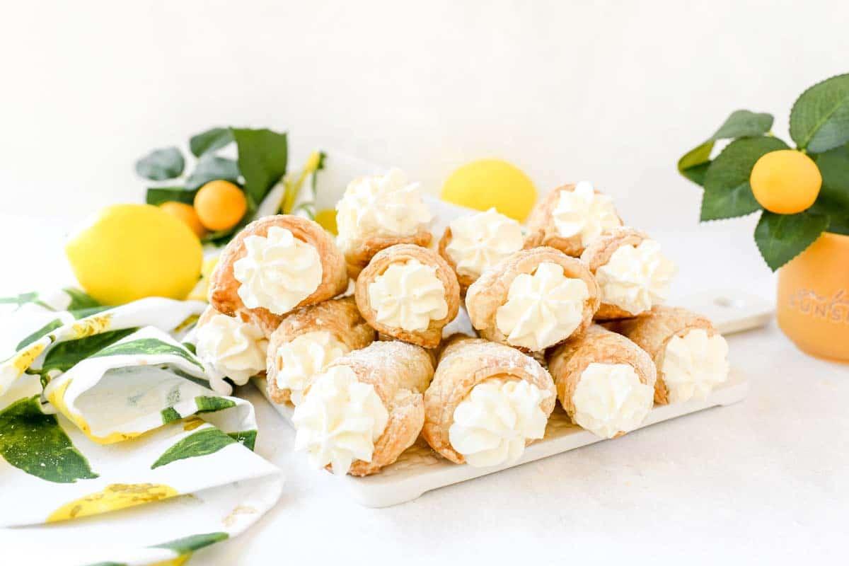 Lemon filled cream horns stacked on a white platter with a lemon napkin.