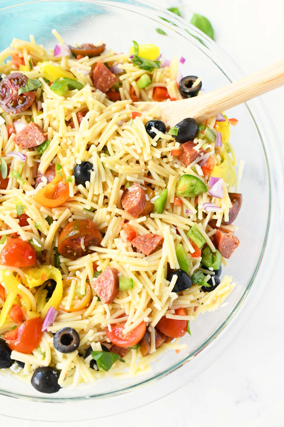 Loaded Pizza Pasta Salad in a glass bowl with a wooden spoon.