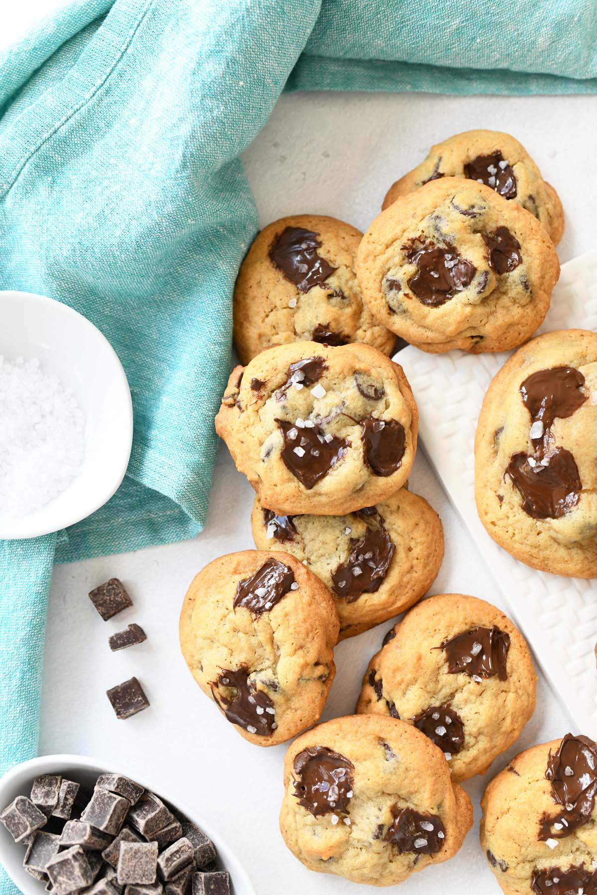 Sea salt and chocolate chip cookies with a blue napkin spread on a white table.