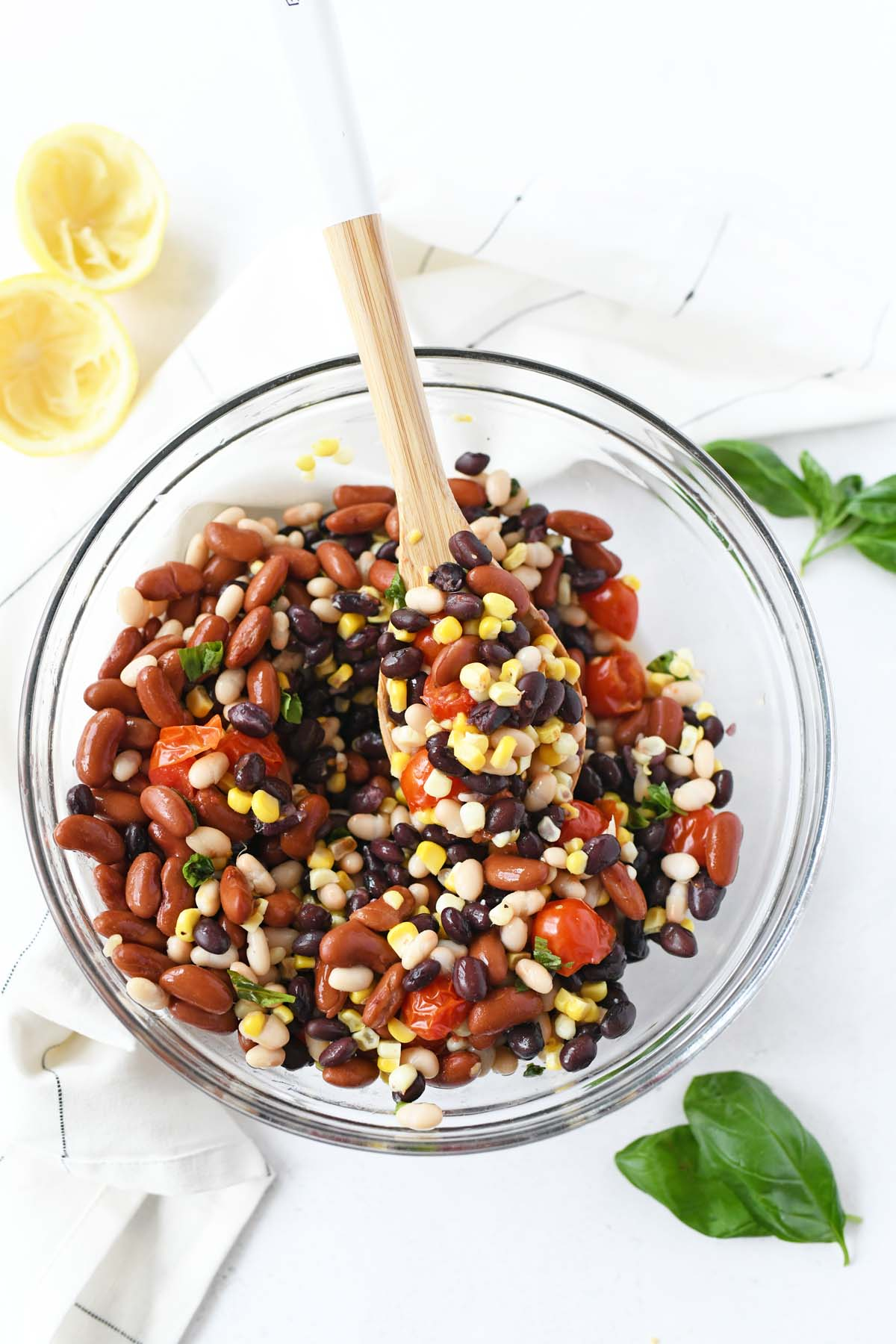 3 bean salad in a glass bowl with a wooden spoon.
