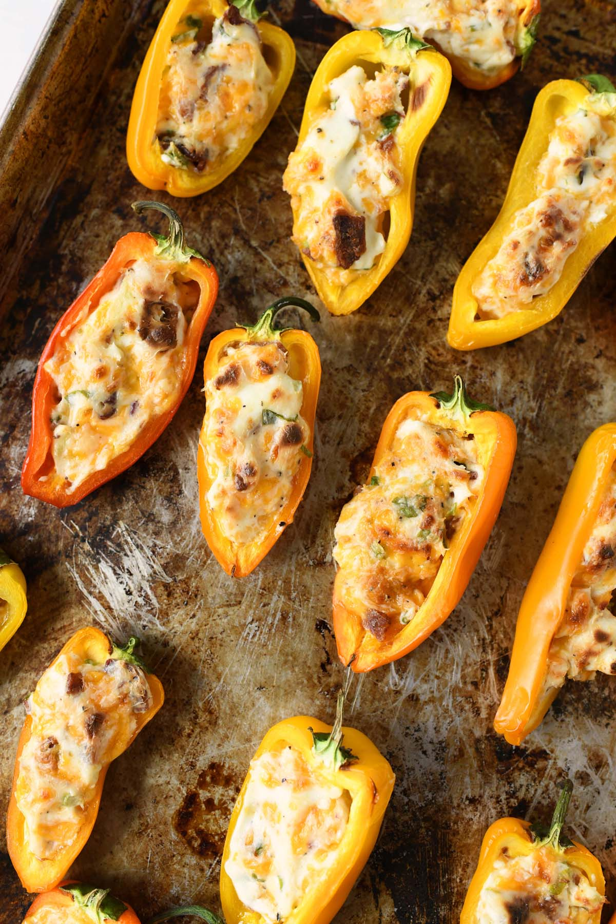 Bacon and cheese stuffed peppers on a baking sheet.