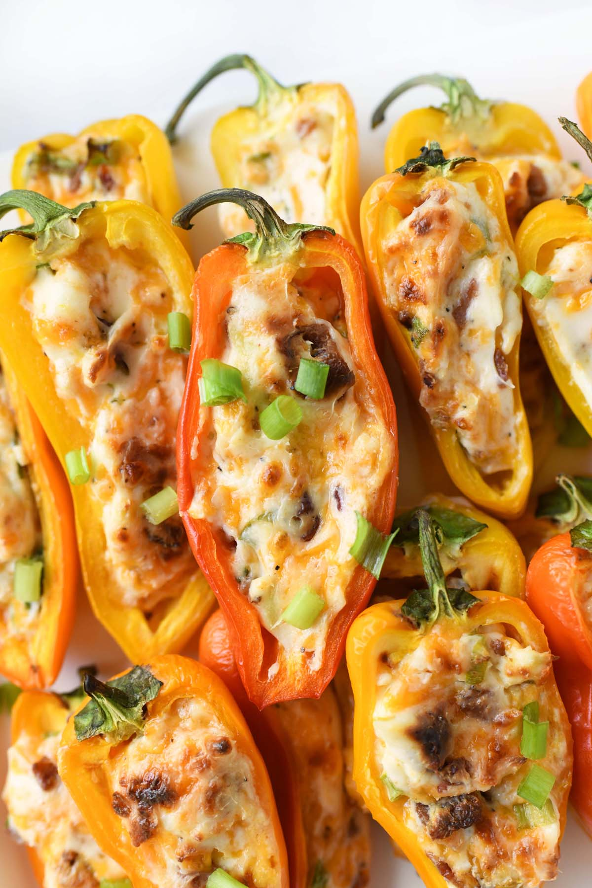 Bacon and cheese sweet peppers stacked on a white tray.