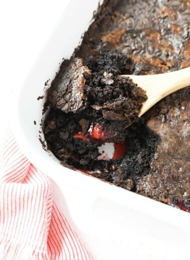 A spoon scooping out chocolate cherry dump cake.