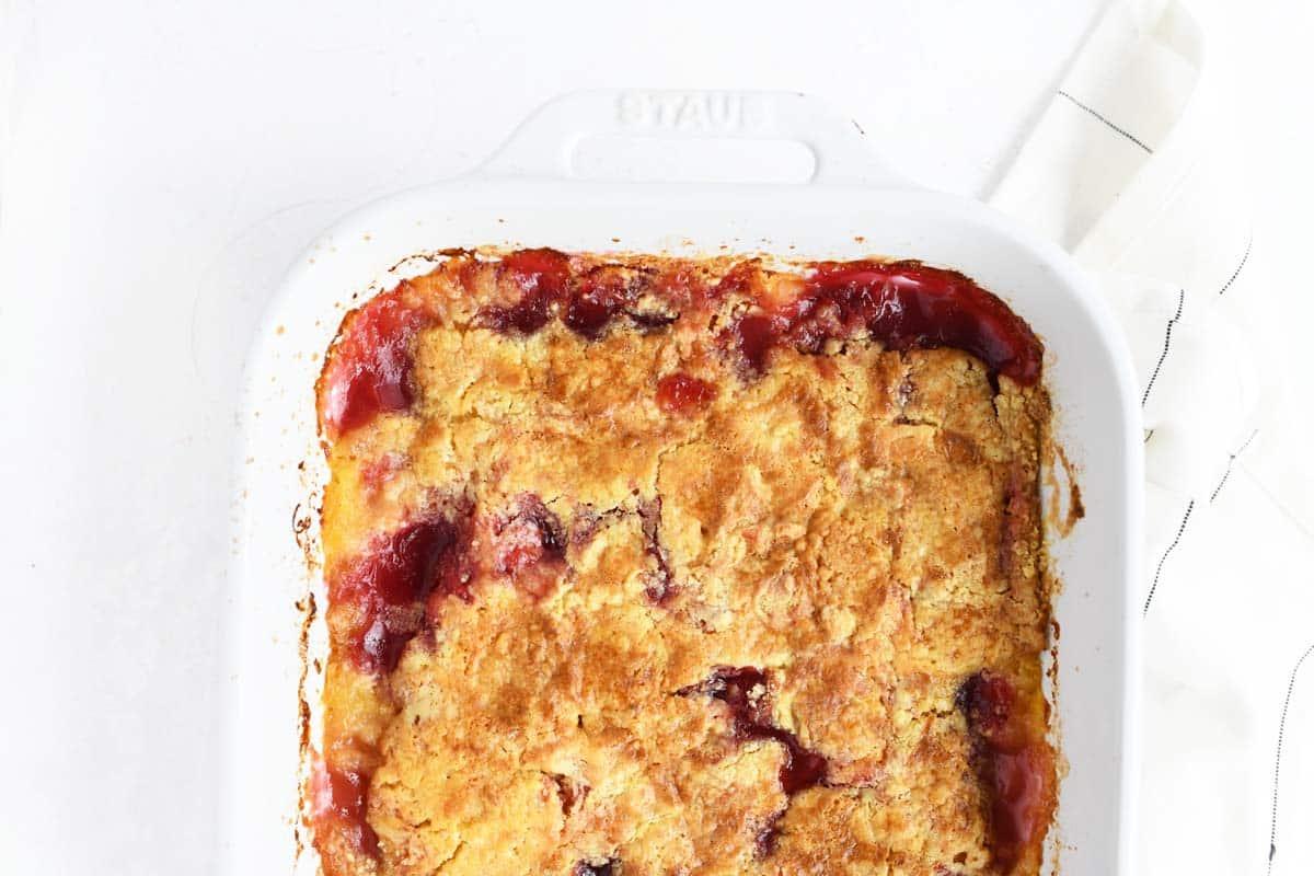 Cherry pineapple dump cake in a white rectangle baker.